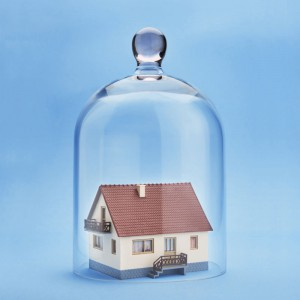 Home safety. A model home protected under a glass dome on blue background